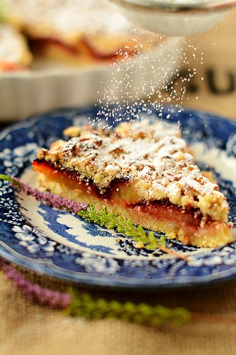 A slice of plum cake being sprinkled with icing sugar