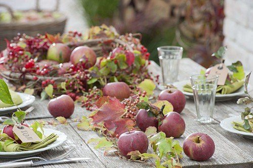 Table decoration with apples, rose hips and wild wine