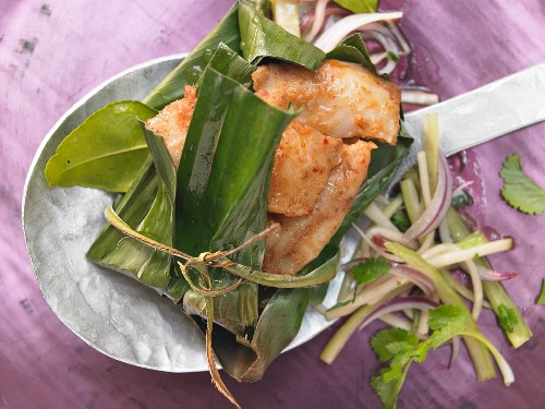 Pangasius fillet steamed in a banana leaf with a green papaya salad