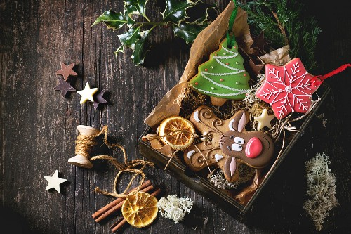 Christmas Handmade patterned gingerbreads as Christmas tree, reindeer Rudolph and snowflake shapes in wooden box