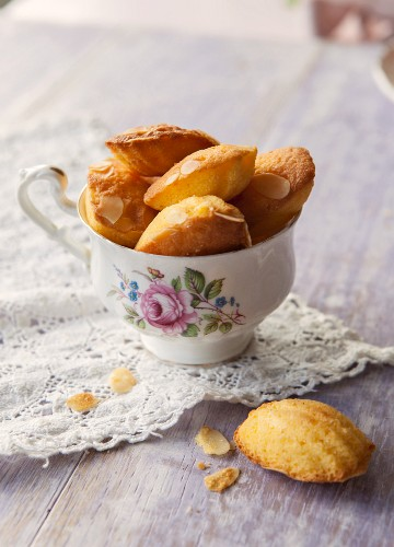 A vintage tea cup full of madeleines on a lace doily