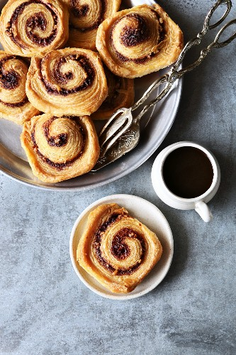 Puff pastry cinnamon rolls on tray with a cup of coffee