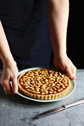 Female hands holding a caramel nut tart on a plate