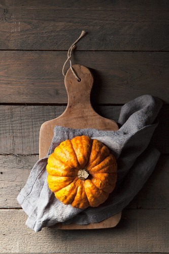 A munchkin pumpkin on a rustic wooden background with a grey linen napkin