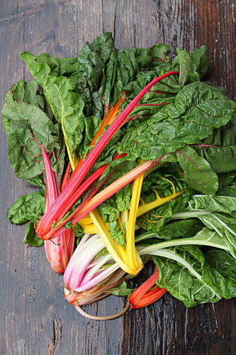 Various different coloured chard on a wooden surface