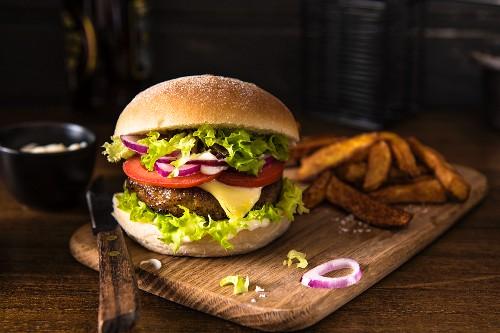 Cheeseburger mit Tomaten, Zwiebeln und Salat, dazu Pommes frites