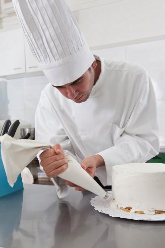 Hispanic chef decorating cake