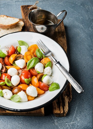 Italian Caprese salad with cherry tomatoes, small mozzarella and fresh basil in white enamel plate