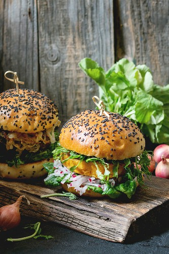Two Homemade veggie burgers with sweet potato, fresh radish and pea sprouts, served on wooden chopping board
