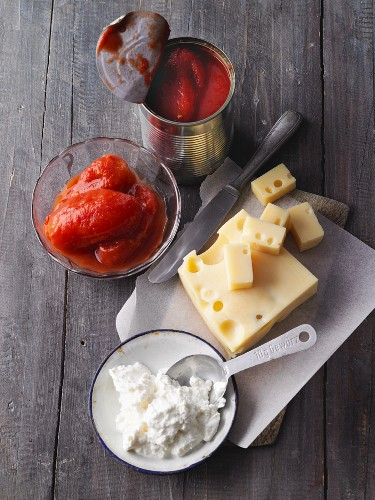 Ingredients for pizza: ricotta, Emmental and tinned tomatoes