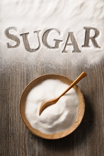Sugar in a wooden bowl and spilled on a wooden background with the word 'sugar'