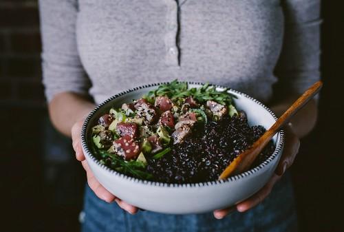 Frau hält Salatsschüssel mit Seared Thunfisch in Sesamkruste und schwarzem Reis