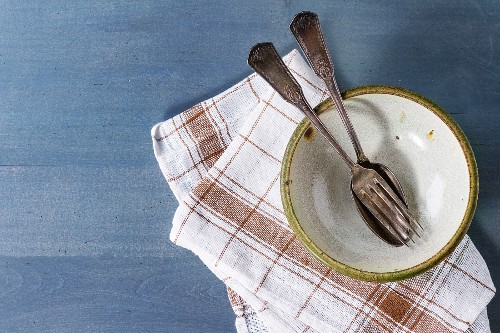 Empty ceramic bowl with vintage cutlery on kitchen checkered towel over blue wooden surface