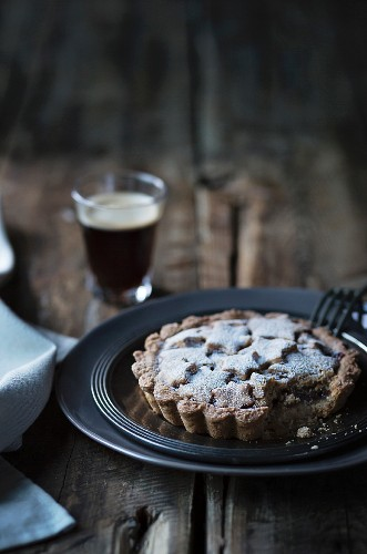 Tart with a glass of coffee on wooden table