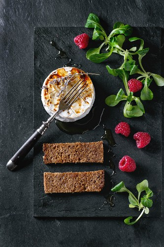 Grilled goat cheese served with liquid honey, lavender, raspberries, wholegrain toast and green salad