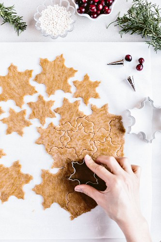A woman is using a cookie cutter to shape a cookie dough with her right hand