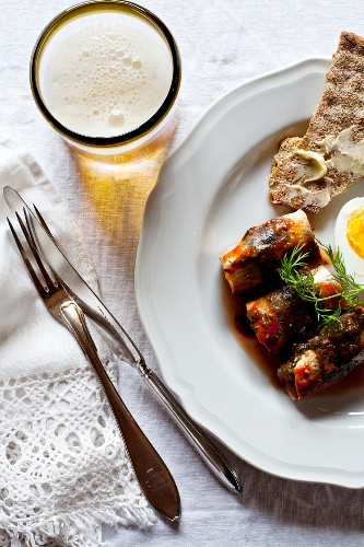 Herring rolls in tomato sauce with egg, crispbread and beer (Sweden)