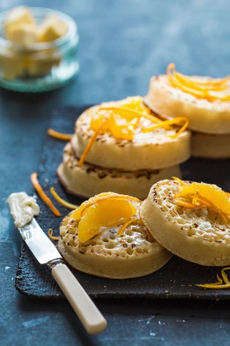Crumpets with orange wedges and orange zest