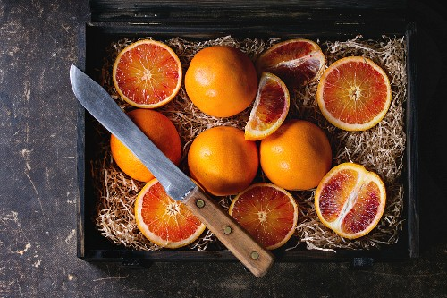 Sliced and whole Sicilian Blood oranges fruits in black wooden box with sawdust over dark background