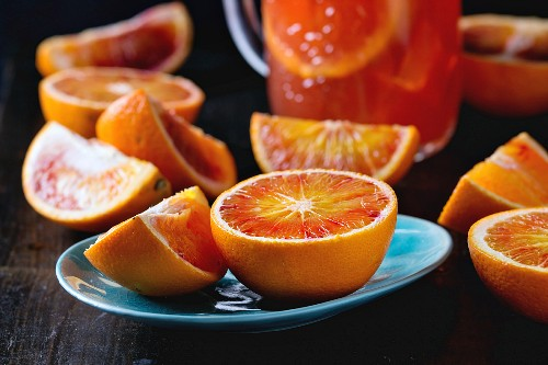 Sliced Sicilian Blood oranges in turquoise ceramic plate and glass mason jar of fresh red orange juice