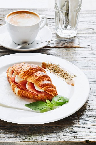 Croissant with mozzarella and ham served on white plate in a Cafe