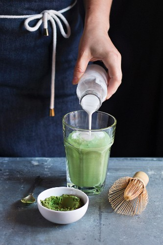 Female hands pouring coconut milk into matcha latte