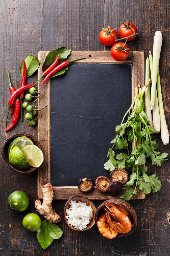 Ingredients for spicy Thai soup Tom Yam with Coconut milk, Chili pepper and Seafood on vintage slate chalk board
