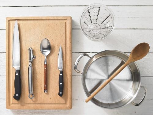 Verschiedene Küchenutensilien: Topf, Messbecher, Messer, Löffel, Sparschäler