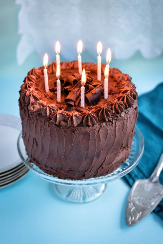 Chocolate birthday cake with 8 lit candles on cake stand