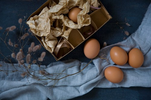 Decorated chickens eggs with a vintage box, a twig and pastel blue fabric
