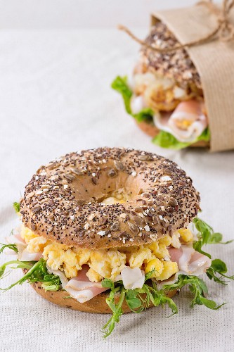 Whole Grain bagels with scrambled eggs, pea sprout and prosciutto ham on wood plate