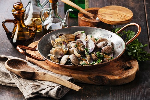 Shells vongole venus clams with parsley in copper cooking dish on dark wooden background