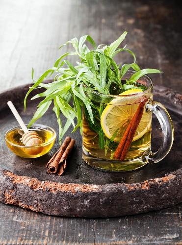 Heisser Tee mit Estragon, Honig, Zitrone und Zimt in Glastasse