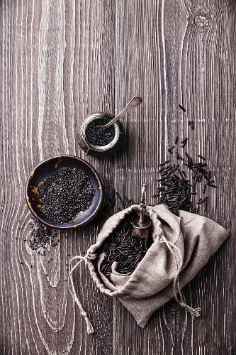 Black raw food ingredients - wild rice, sesame seeds, black salt on gray wooden background
