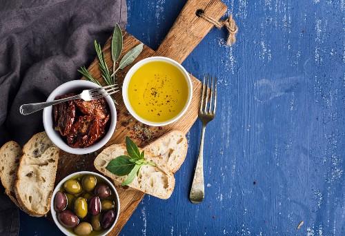 Mediterranean snacks set. Olives, oil, herbs and sliced ciabatta bread on yellow rustic oak board