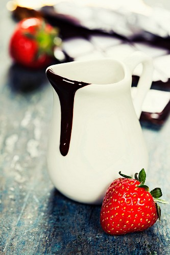 Delicious rich and thick chocolate sauce in a jug and assorted chocolates