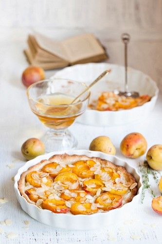 Breakfast with homemade apricot tarte with almonds, fresh apricots and honey on white wooden table