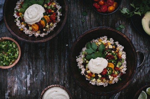 Two bowls of Mexican Burrito Bowl with cashew cream sauce surrounded