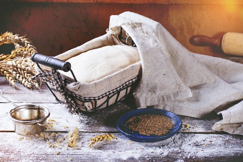 Dough in proofing basket on wooden table with flour, cumin and wheat ears