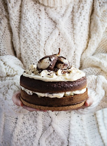 Woman s hands holding a chocolate cake