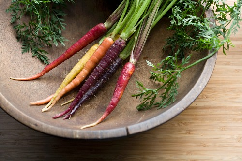 Rainbow carrots in an old wooden bowl