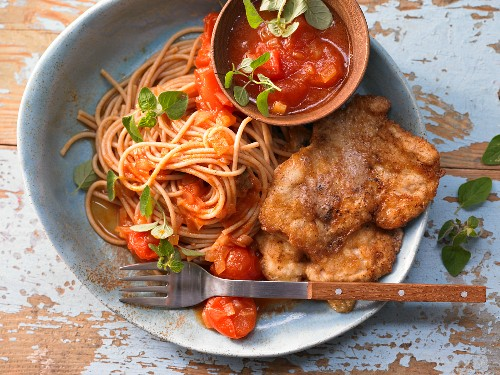 Chicken breast slices in a cheese coating with noodles and tomatoes