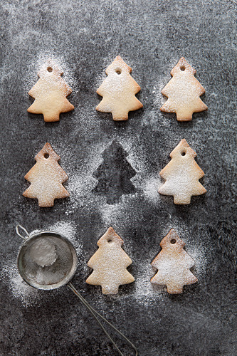 Rows of Christmas tree shaped biscuits dusted with icing sugar with one missing with just the outline remaining and a mini sifter filled with icing sugar all on a grey slate surface