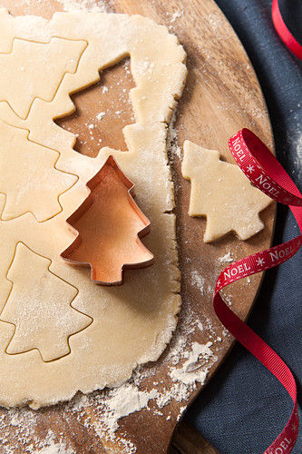 Cookie dough rolled out on a floured wooden board with a copper tree shape cookie cutter cutting out tree shape bluwe napkin and noel red ribbon