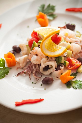 Seafood salad with squid, prawns, courgettes, olives and cherry tomatoes