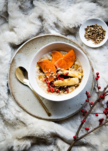 Wholegrain porridge with chai spices and topped with persimmon, banana, goji berries and sunflower seeds