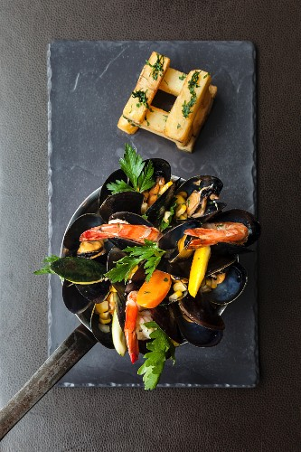 A pan of mussels with prawns, corn and vegetables served with a stack of chunky chips