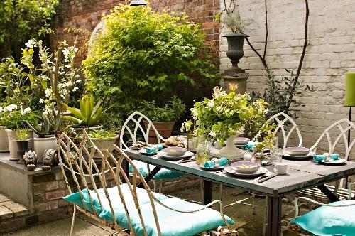Gedeckter Tisch auf Terrasse vor Topfpflanzen und Gartenmauer