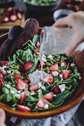 A woman is pouring poppy seed dressing into a strawberry and spinach salad
