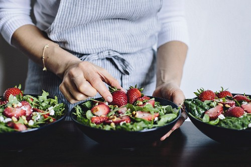A woman is placing a strawberry into a bowl of strawberry spinach and arugula salad